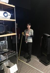 プロジェクター投写距離をメジャーで測る細井