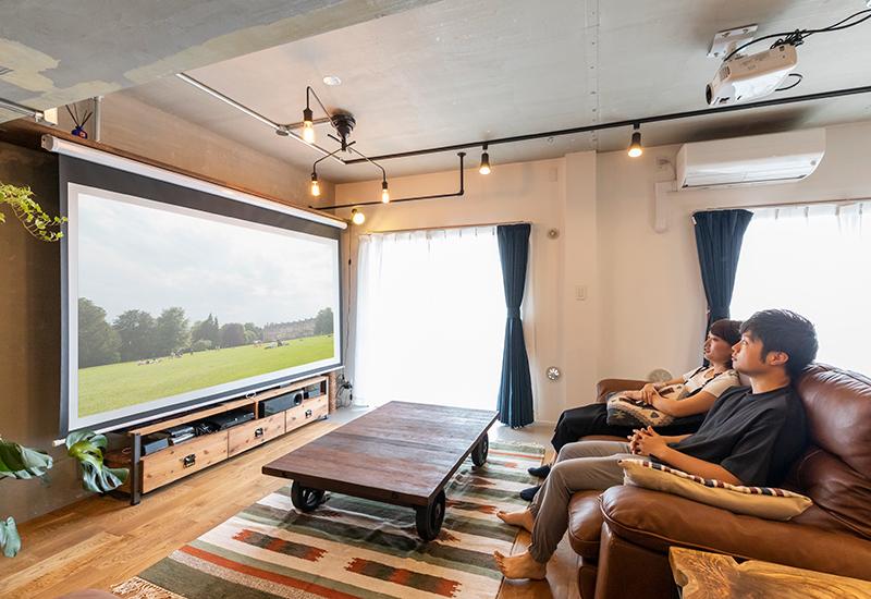 リノベーションしたリビングのソファで、ホームプロジェクターの映像を楽しむUさんご夫婦