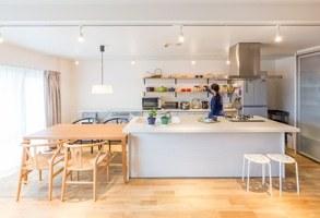 ワイドなキッチンが佇むさわやかな空間と、室内窓のアクセント