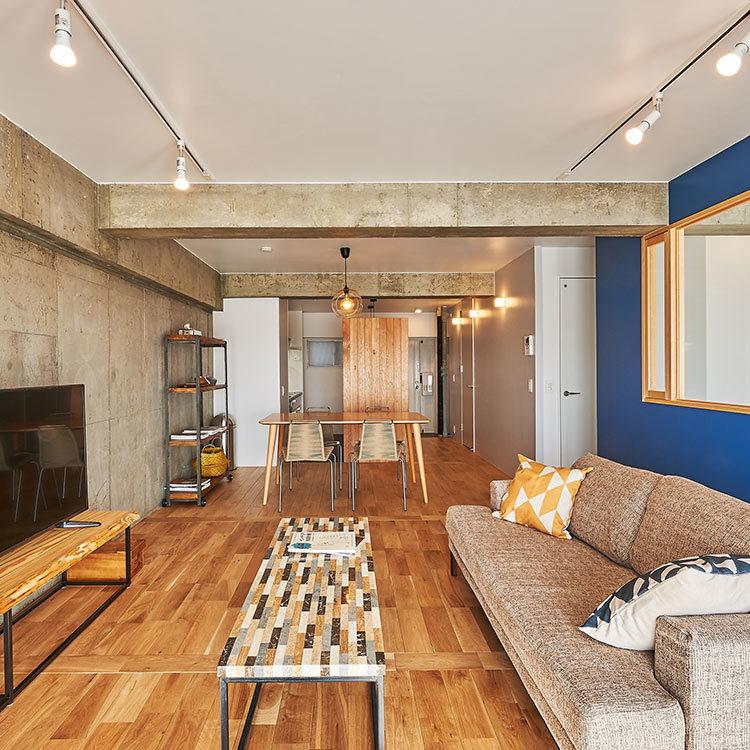 青い塗装壁と大きな室内窓がアクセントになった見通しのいいリビング